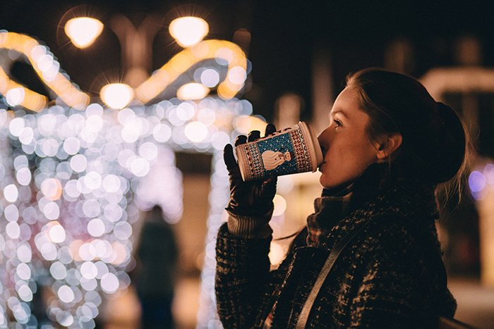 Beautiful Christmas bokeh lights in the background of a portrait of a girl drinking coffee
