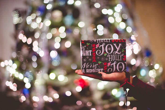 Beautiful Christmas bokeh lights in the background of a person holding a gift
