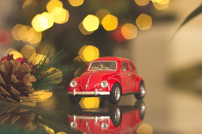 Beautiful Christmas bokeh lights in the background of a small car