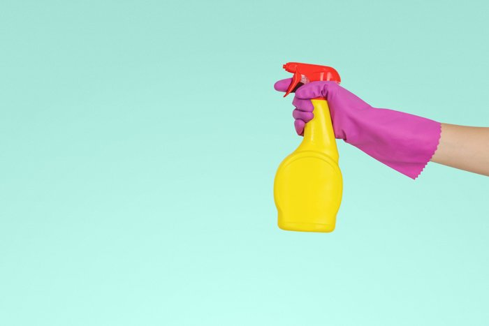 a hand holding a squirt bottle against a teal background