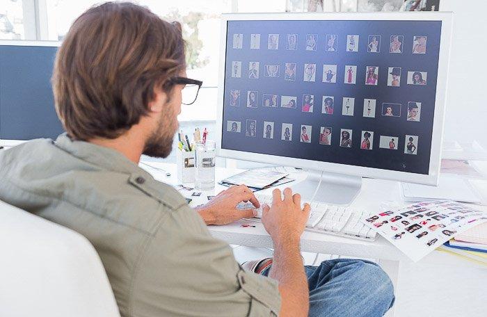 A photographer editing stock photos on a computer
