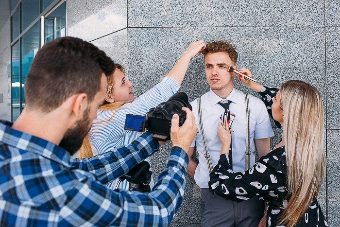 Two stylists attending a male model during a photo shoot