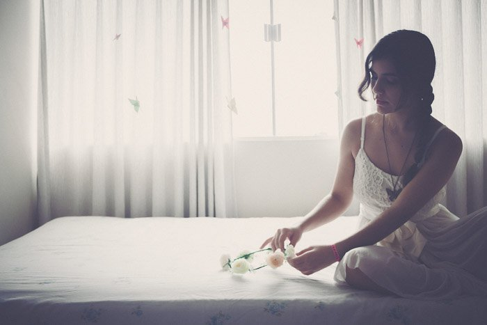 Bright and airy glamour shots of a female model posing on a bed