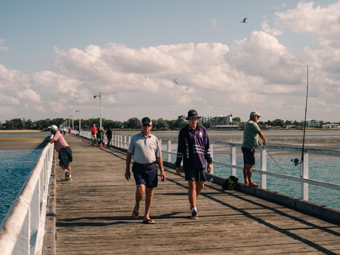 A wooden promenade with many people walking or standing
