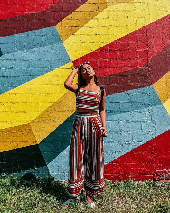 A female model posing by a multi colored wall taken with an iphone photo timer