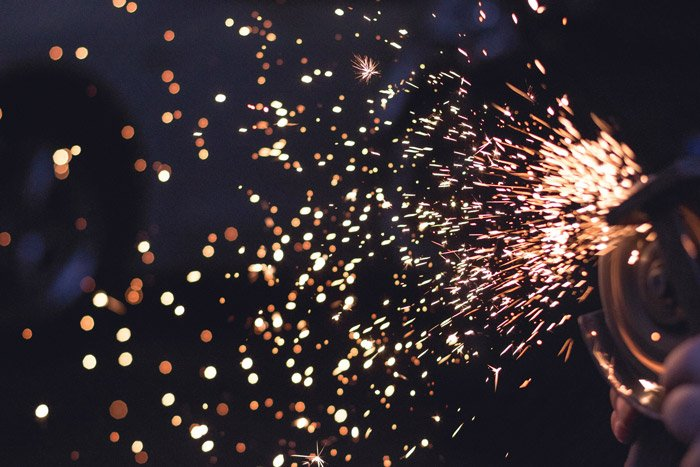 Close up shot of sparks flying from industrial machinery in low light
