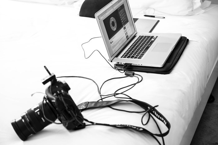 A black and white photo of a DSLR camera attached to a laptop