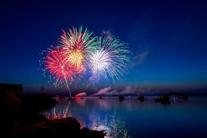 Photo of colorful fireworks above a river