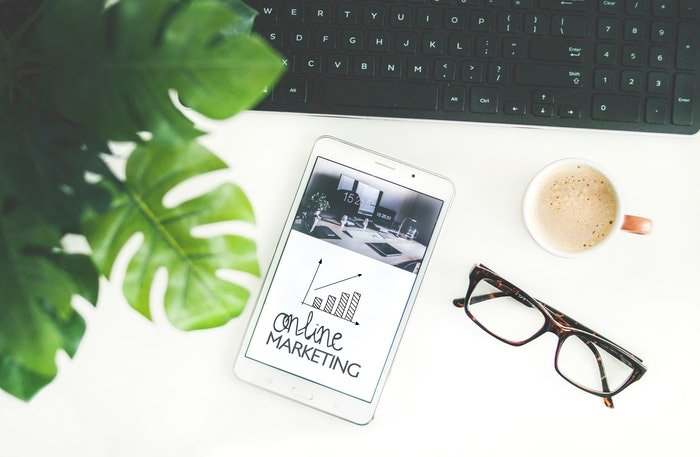 A flat lay of a plant, glasses and a smartphone with the screen reading 'online marketing'