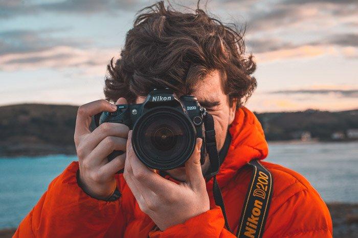 A man in orange jacket holding a Nikon DSLR camera