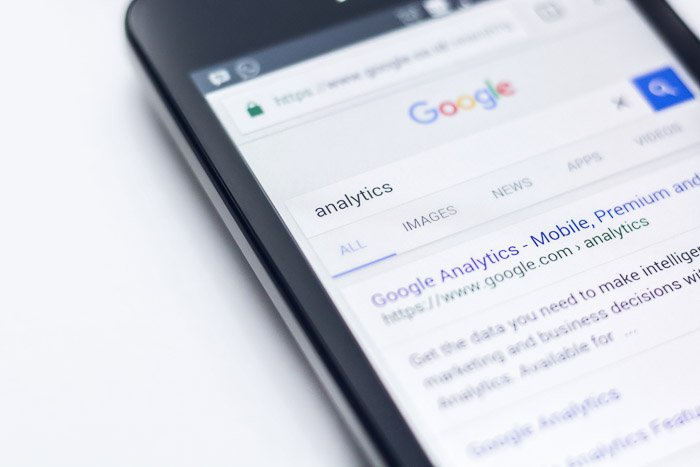 A close up of a smartphone searching for google analytics
