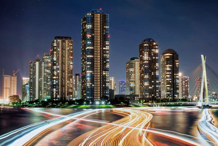 A sprawling cityscape with streaming colored light trails
