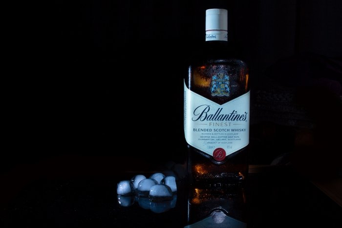A Ballantines whisky bottle with ice cubes next to it on a black background