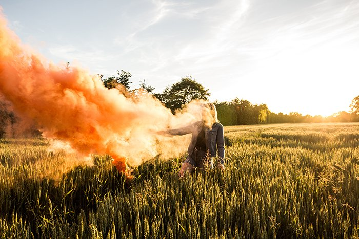A portrait of a woman holding orange smoke grenades in a cornfield