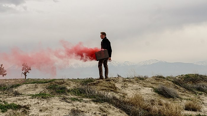 Atmospheric portrait of a woman holding red smoke grenades