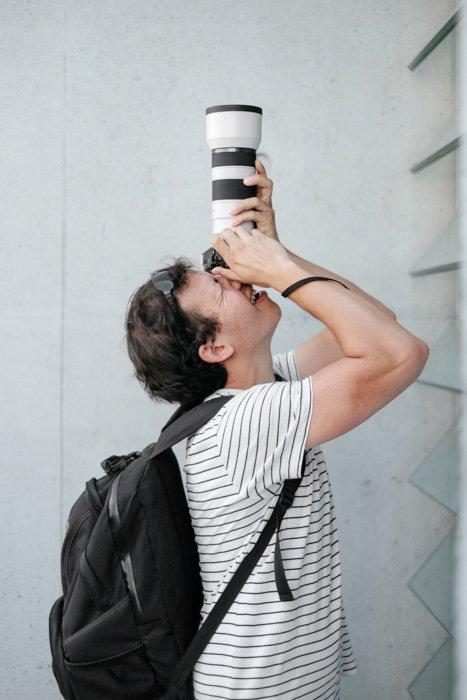 A photographer shooting through a DSLR camera with a teleconverter
