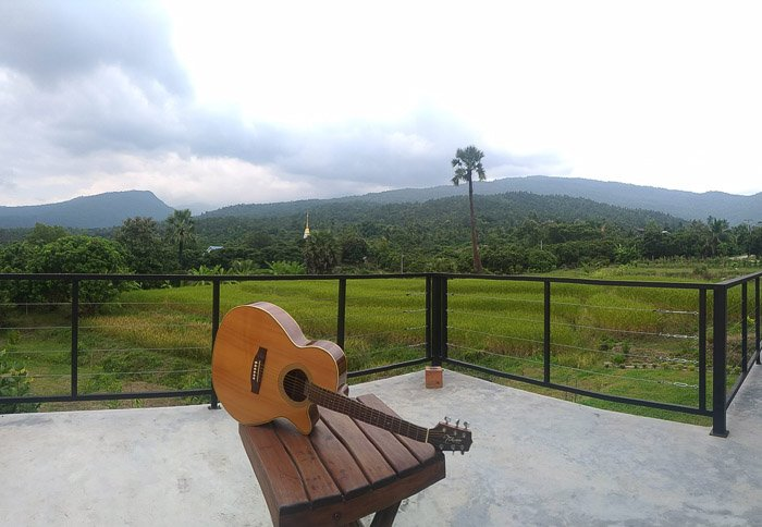 A guitar resting on an outdoor table