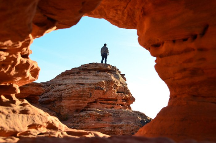 A man standing on a red rock shot through a cave , processed with adobe camera raw editor