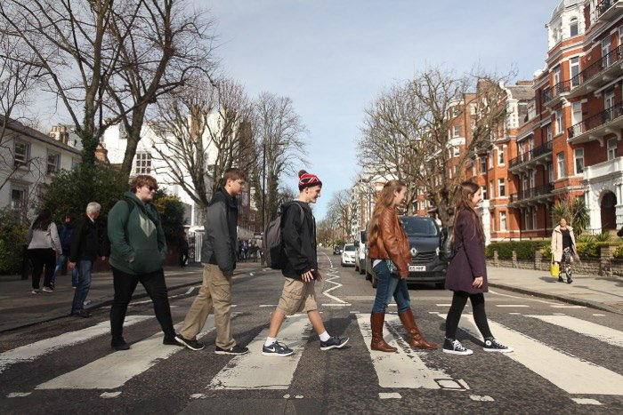 A group of 5 people crossong the street in Abbey road in the style of the Beatles