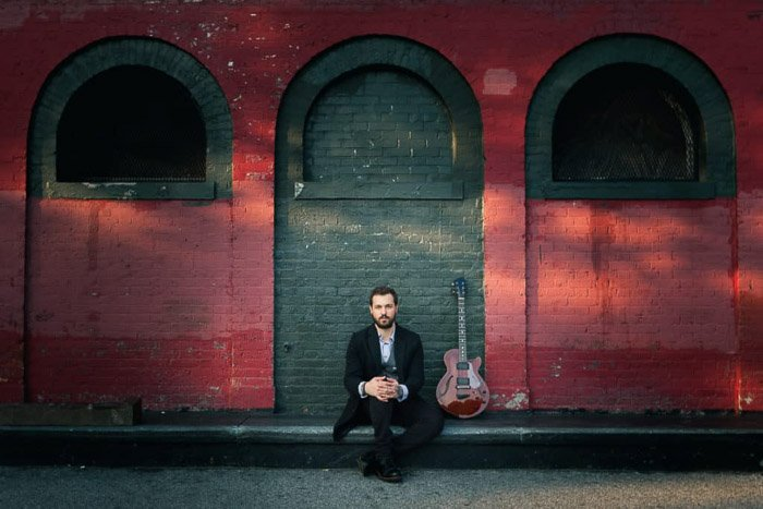 A color portrait of a musician posing in front of a red wall in Brooklyn