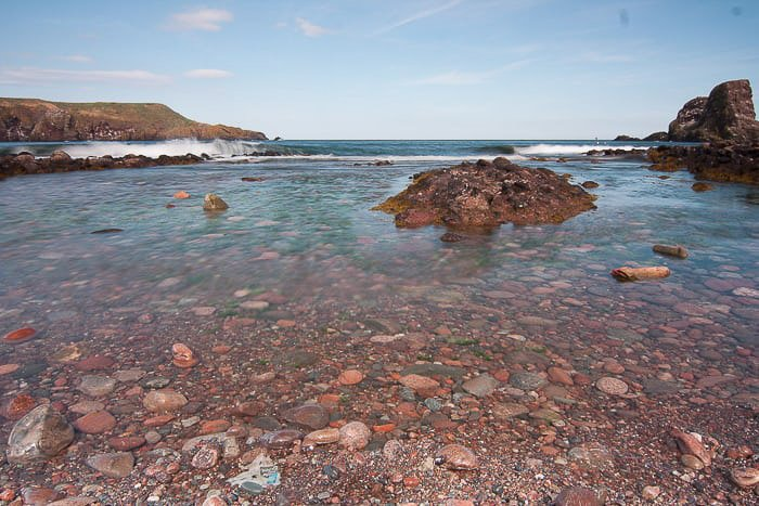 Pretty coastal image with red colored rocks