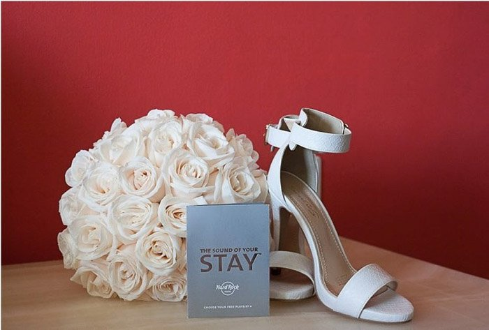 A wedding photography still life featuring a pair of shoes, flowers and booklet