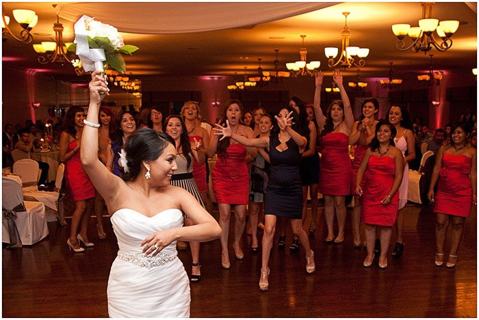 A bride throwing a bouquet at the wedding service - destination wedding photography