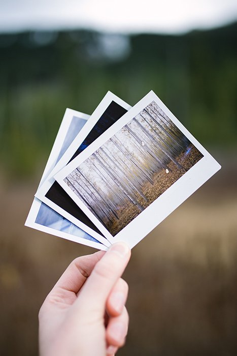 A person holding three polaroid photos - film photography look