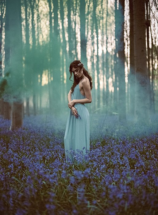 A stunning film photography style portrait of a female model posing in a dreamy forest