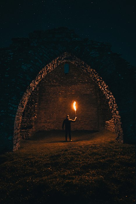 A dramatic and mysterious portrait of a man holding a flame under an arch at night - fire photography tips