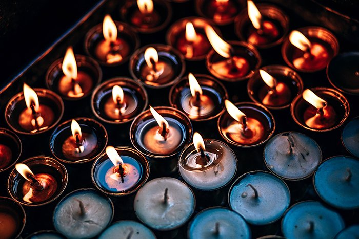 A tray of candles, half are lighting