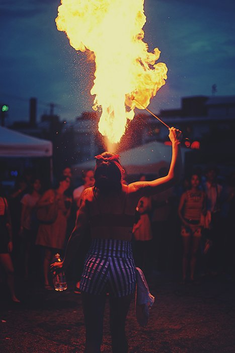 A fire dancer breathing flames during a festival at night