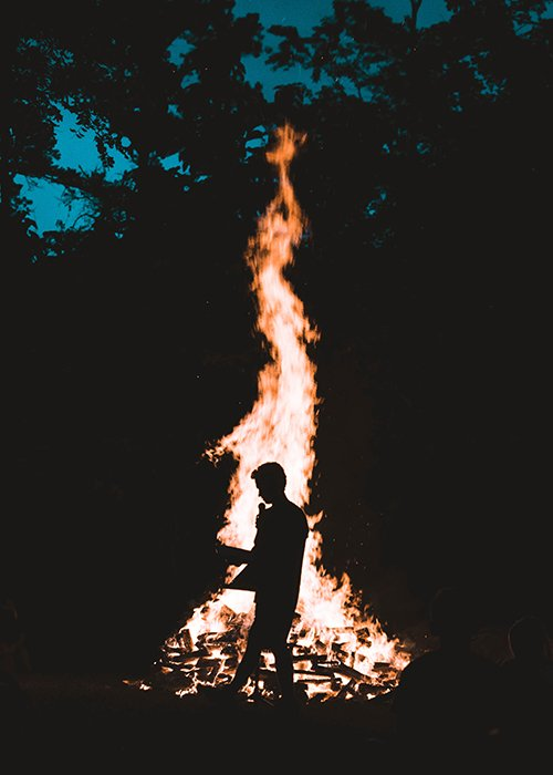 The silhouette of a person in front of a large bonfire - fire photography