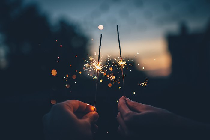 Two hands holding sparklers in low light - fire photography