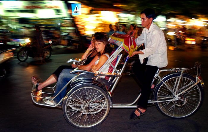 Flash Photography of Tourists in cycle taxi, Hanoi, Vietnam