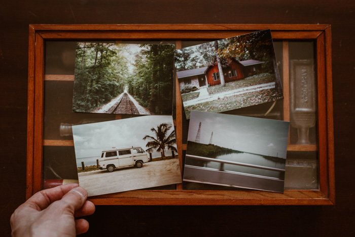 A person placing printed photos together in a wooden frame