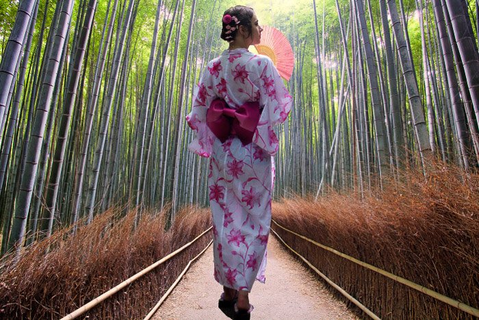 A girl in traditional japanese dress walking through a bamboo forest