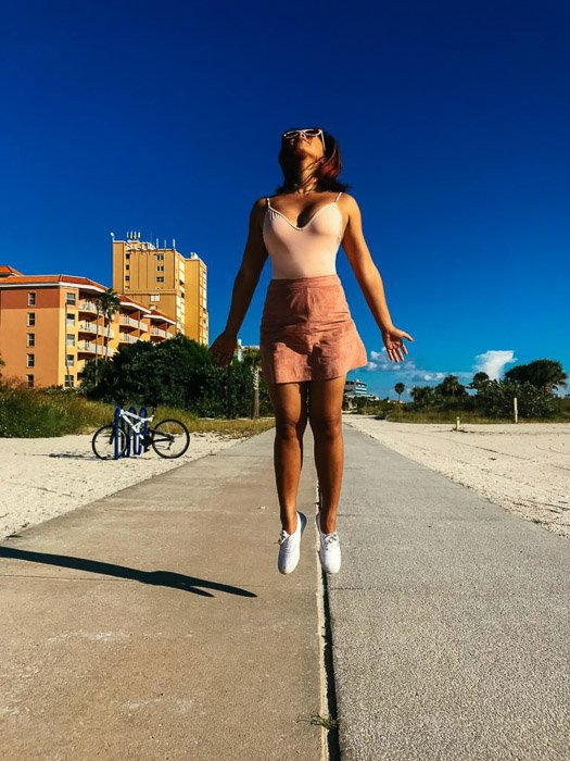 An outdoor photo of a girl jumping on a pavement shot using iPhone burst mode
