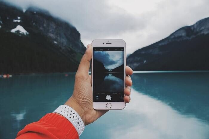 Photo of someone taking a photo with an iphone of a lake