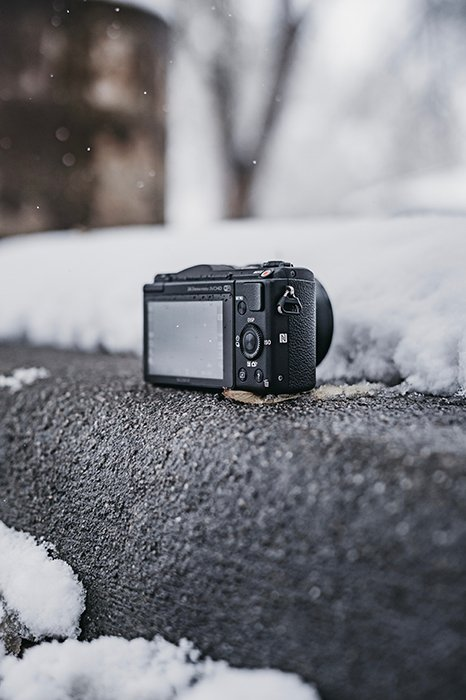 A Canon DSLR camera resting on the snow