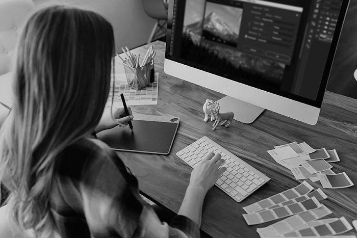 A black and white photo of a girl editing photos on Lightroom 6