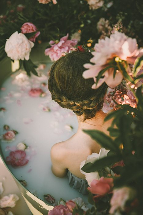 Beautiful milk bath photography of a female model surrounded by flowers