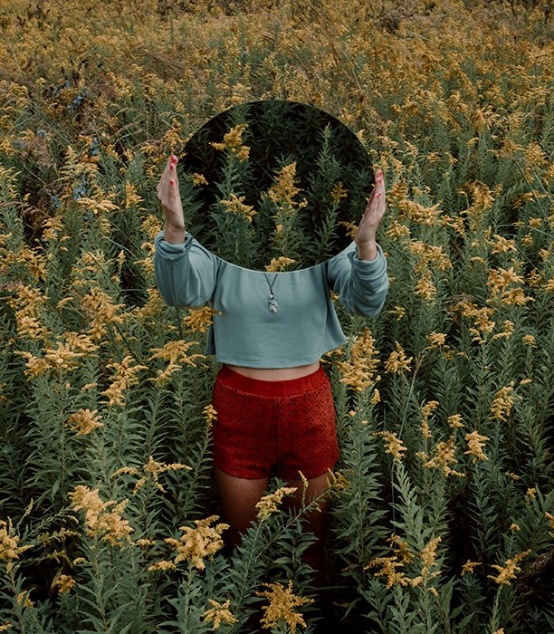 Surreal mirror photography shot of a female model in an overgrown field, holding a mirror over her ace which reflects more overgrown foliage
