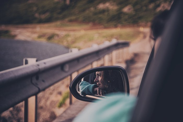 the reflection of a young woman in the side mirror of a driving car