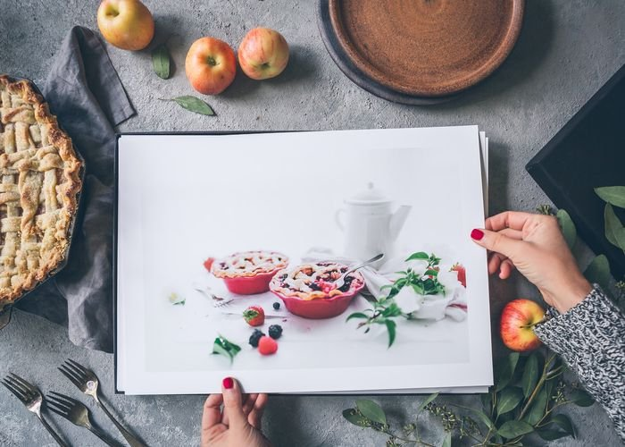 hands holding photo prints of food over a desk with apples and a pie