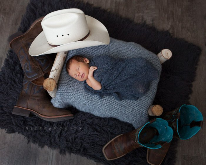 A newborn baby boy on a faux fur blanket surrounded by various newborn photography props