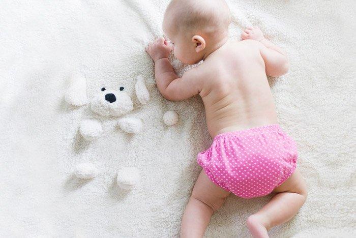 A newborn baby posed on a teddy bear rug