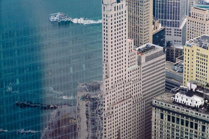 Aerial cityscape with buildings and sea reflected in the glass windows of a neighbouring building - reflection photography tips