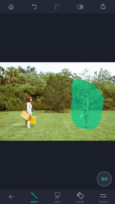 Screenshot of the touch retouch app with two people standing on the field, one of them highlighted by brush selection