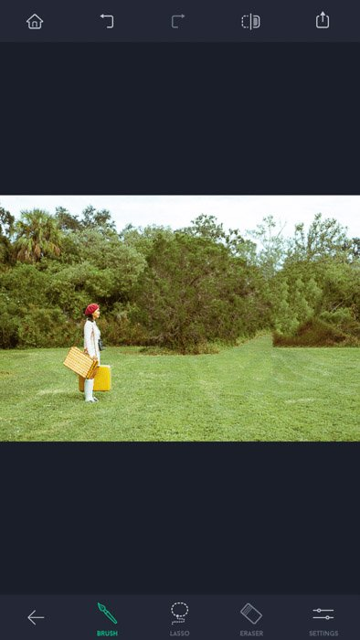 Screenshot of the touch retouch app, a woman with red hat and yellow bags standing on the field